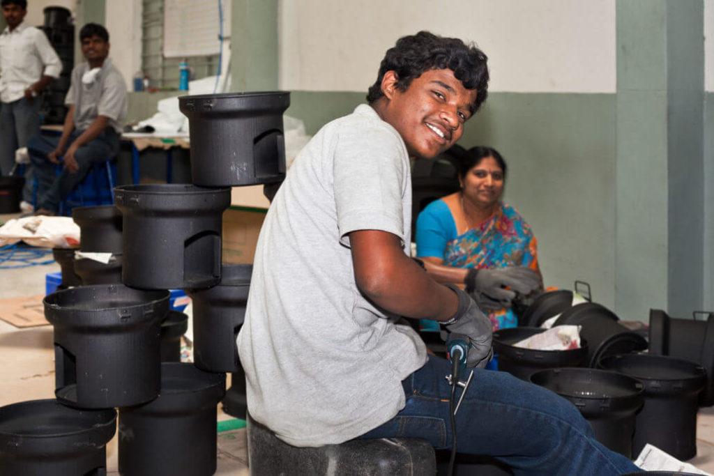Ein junger, indischer Mann baut klimafreundliche Öfen für unser Climate Partner Projekt